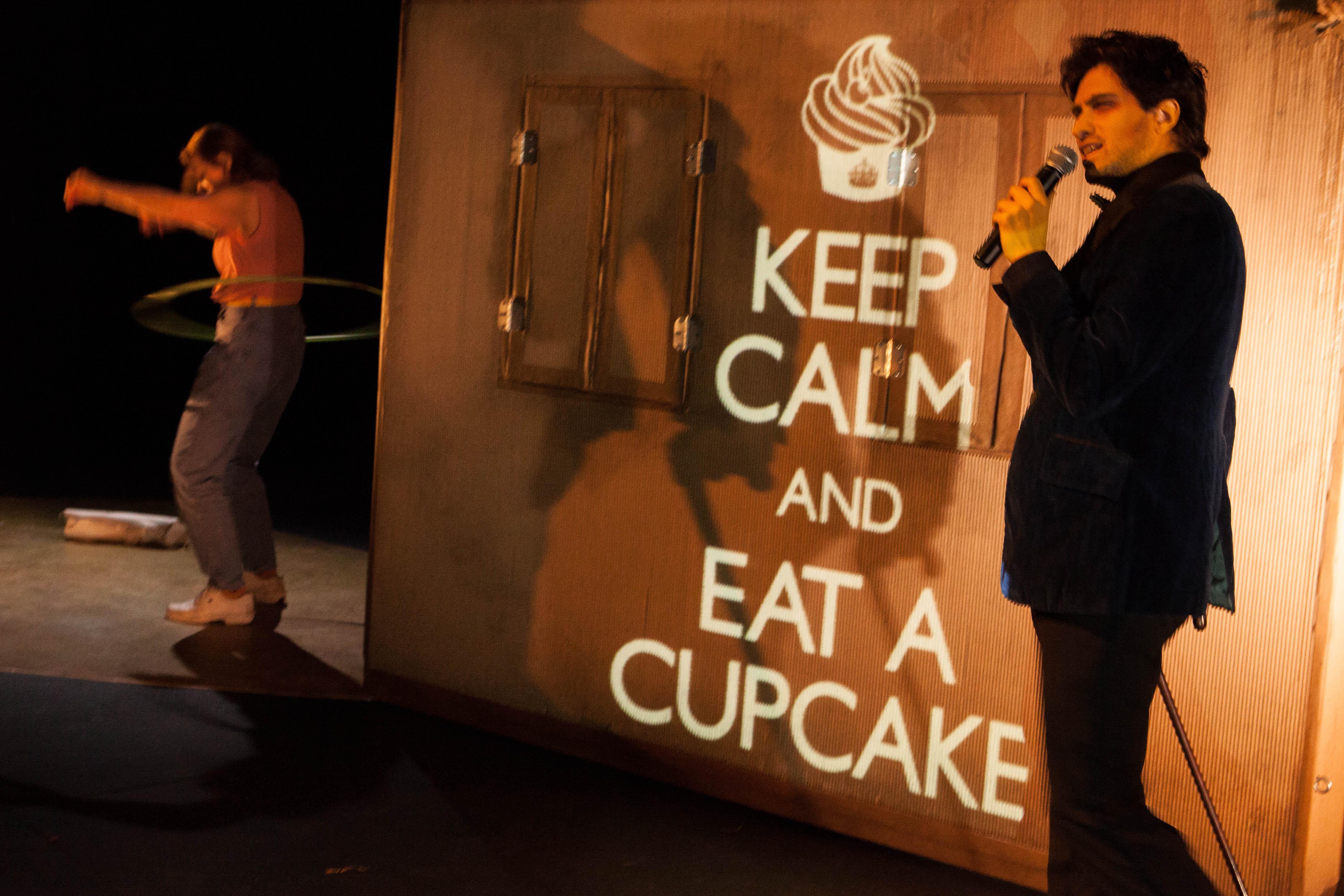 Jacqueline fait tourner un cerceau autour de sa taille; Anthony chante au micro et le texte «Keep Calm and Eat a Cupcake» est projeté sur la maison de carton.
