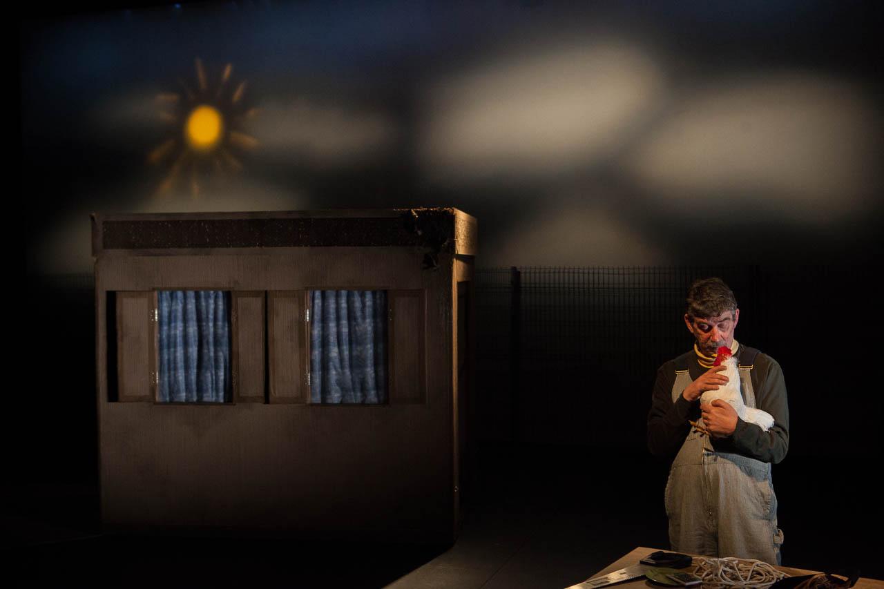 Un soleil jaune surplombe une maison de carton; l'acteur Michael Nimbley flatte affectueusement sa poule.