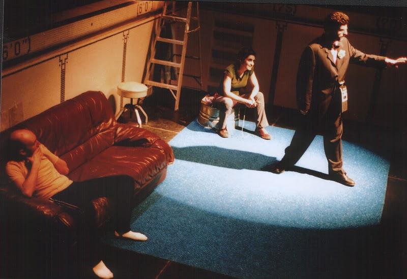 Marc est debout dans un cercle de lumière; derrière lui, Jean-Pascal est assis sur un divan brun et Pascale est assise sur la bassine.