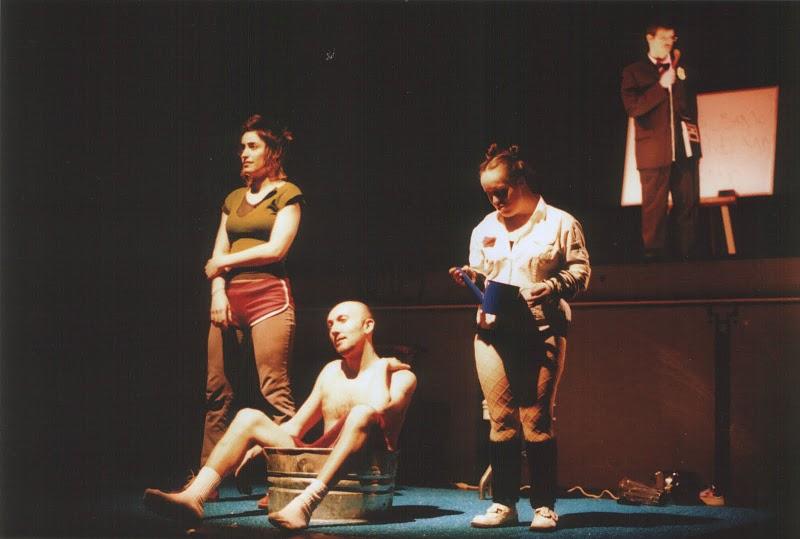 Jean-Pascal est assis, dénudé, dans une bassine de métal, entouré de Pascale et de l'actrice Geneviève Morin-Dupont; derrière eux, en hauteur, l'acteur Marc Barakat parle au micro.