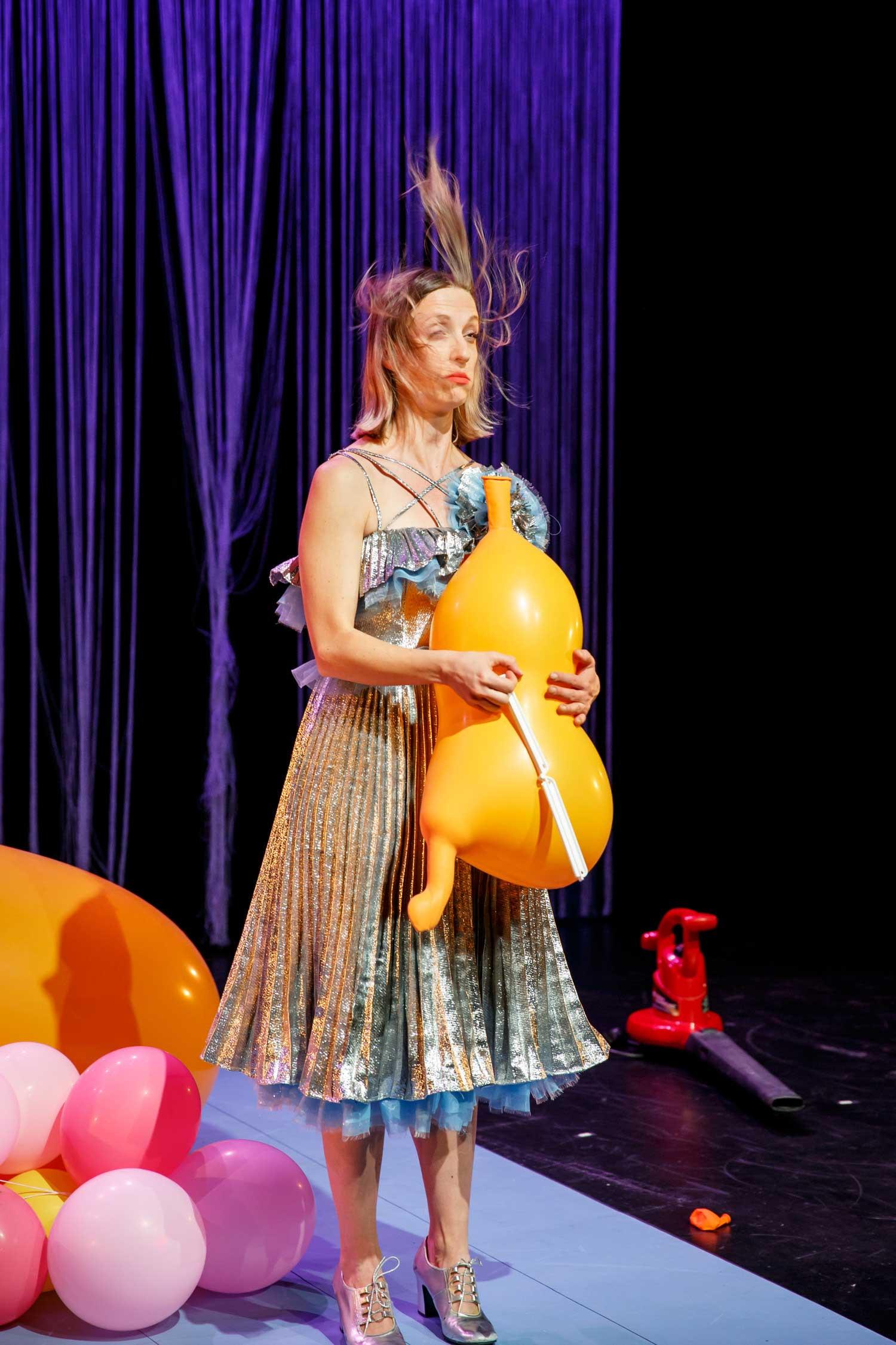 La performeuse Emma-Kate Guimond, en robe argent, a les cheveux ébouriffés par l'air d'un gros ballon orangé qui se dégonfle.