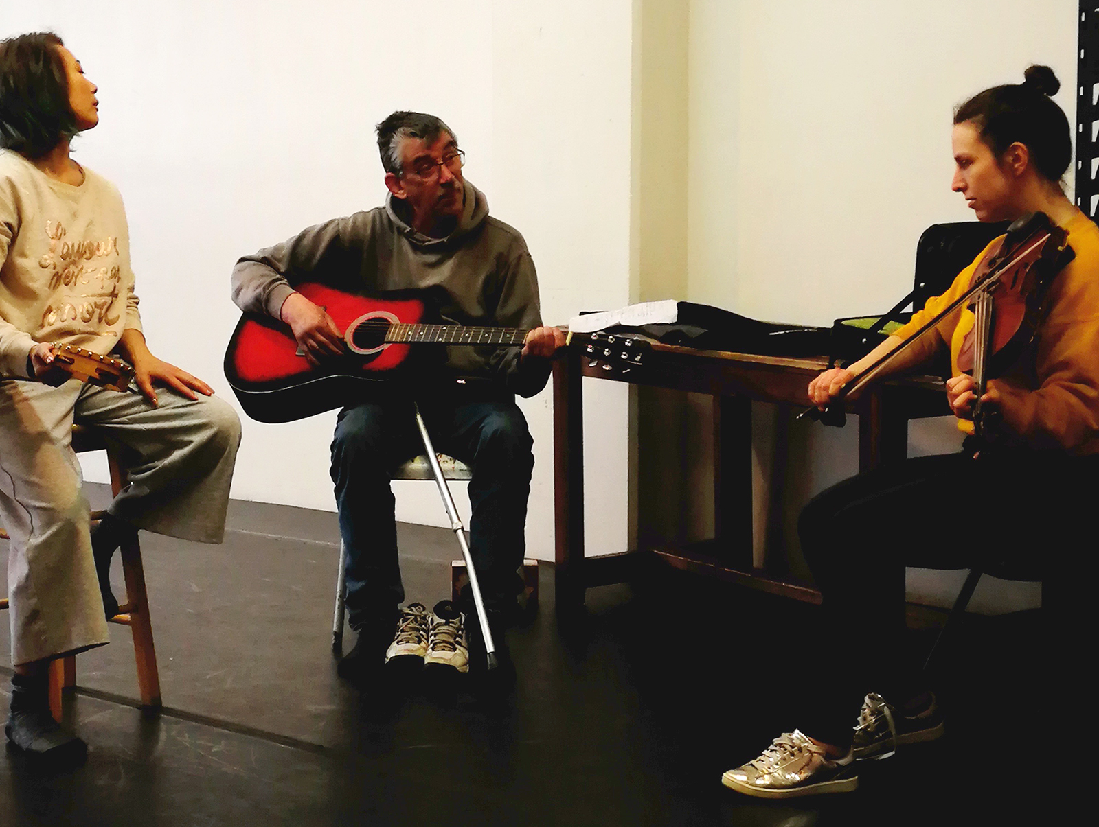 En salle de répétition, la danseuse Angie Cheng joue du tambourin, l'artiste Michael Nimbley joue de la guitare et la musicienne Anna Atkinson joue du violon.
