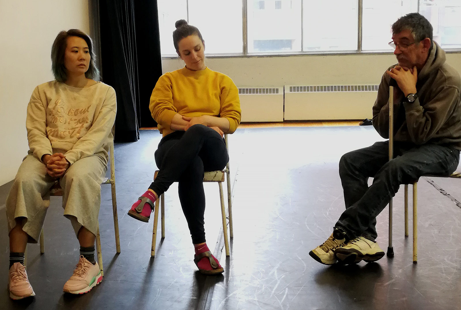 Assis sur des chaises en salle de répétition, les artistes Angie Cheng, Anna Atkinson et Michael Nimbley regardent au sol dans des directions différentes.