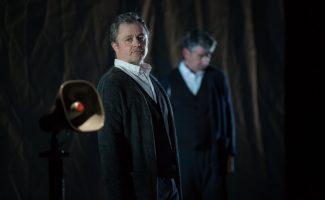 L'acteur Marc Béland regarde un haut-parleur d'un air sérieux, pendant que l'acteur Michael Nimbley baisse la tête au deuxième plan.