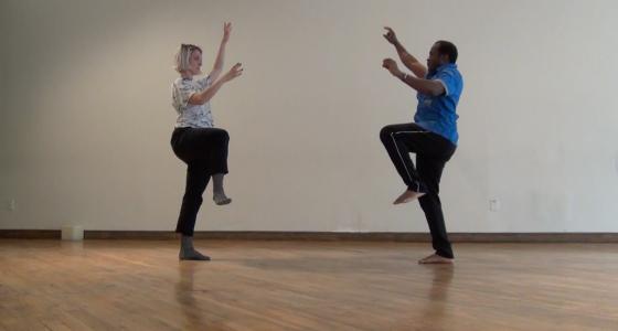 Dans une salle de répétition, la performeuse Emma-Kate Guimond et l'artiste multidisciplinaire Edon Descollines dansent symétriquement, l'un face à l'autre.