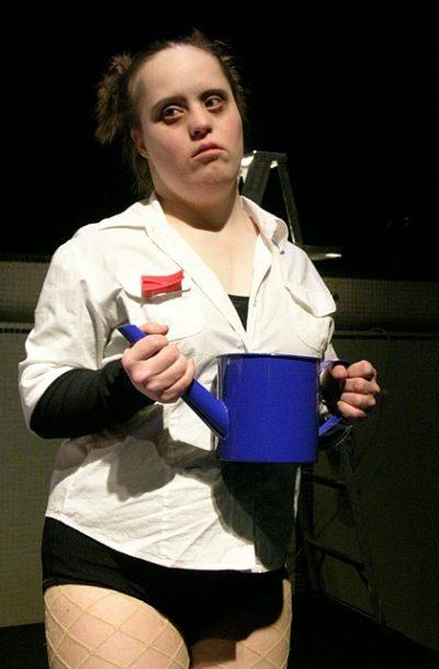 Geneviève tient un arrosoir bleu, l'air sérieuse.