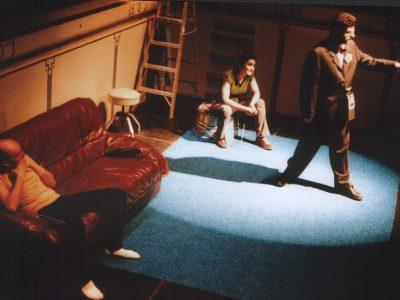Marc est debout dans un cercle de lumière; derrière lui, Jean-Pascal est assis sur un divan; Pascale est assise sur la bassine.