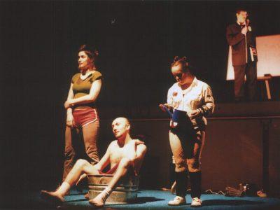 Jean-Pascal est assis, dénudé dans une bassine de métal, entouré de Pascale et de l'actrice Geneviève Morin-Dupont; derrière eux, l'acteur Marc Barakat parle au micro.